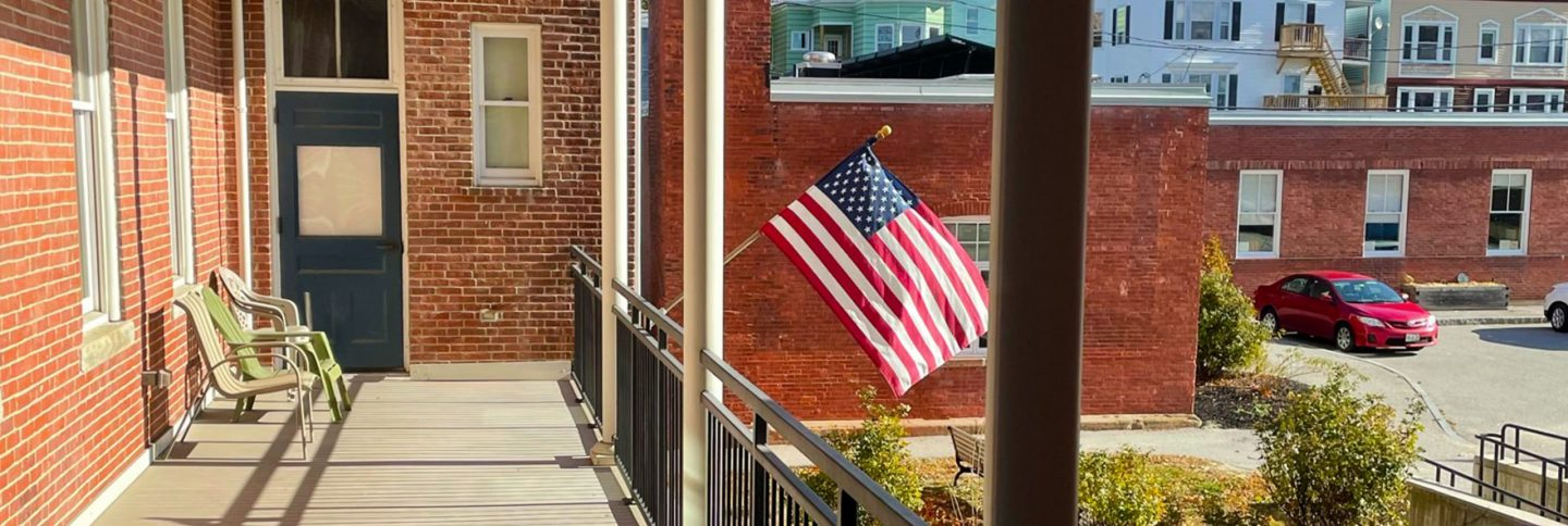 A sunny day back porch at Healy Terrace in Lewiston, Maine